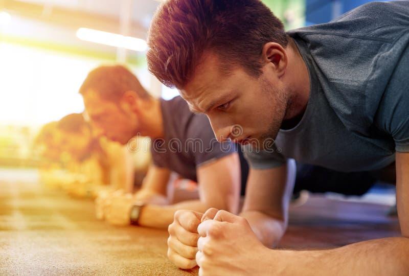 Obsługuje robić deski ćwiczeniu przy grupowym szkoleniem w gym obrazy stock
