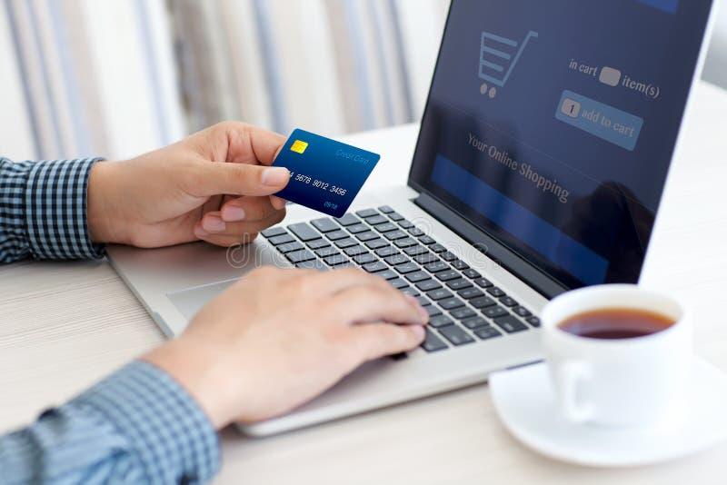 Obsługuje robić online zakupy z kredytową kartą na laptopie zdjęcie stock