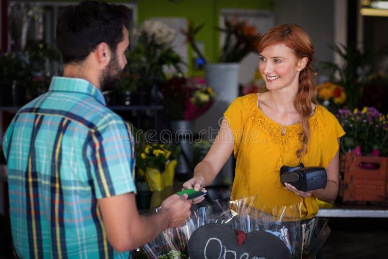 Obsługuje robić zapłacie z jego kredytową kartą żeńska kwiaciarnia fotografia stock