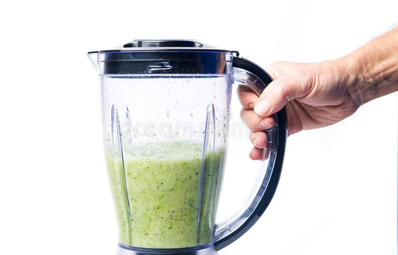 Obsługuje robić zielonemu smoothie pić w blender obraz stock