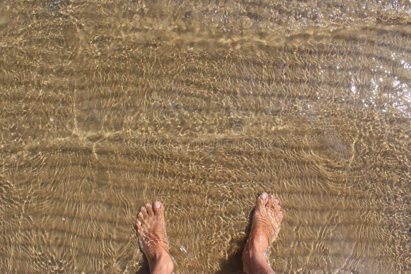 OBSŁUGUJE ` S cieki NA brzeg morze fotografia royalty free