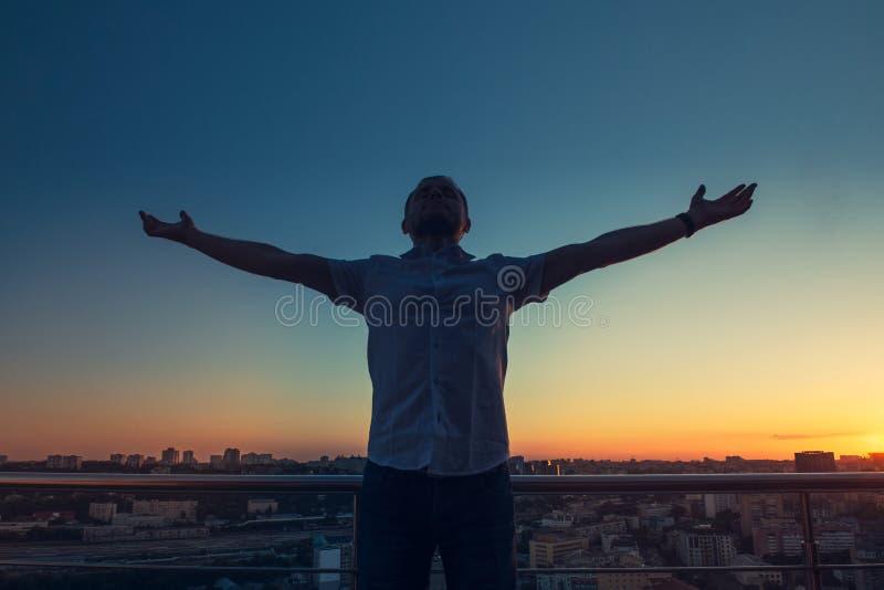 Obsługuje ` s sylwetkę z rękami rised do nieba na zmierzchu pejzażu miejskiego bacground Czujący wolność i świętujący, zwycięstwo zdjęcia royalty free