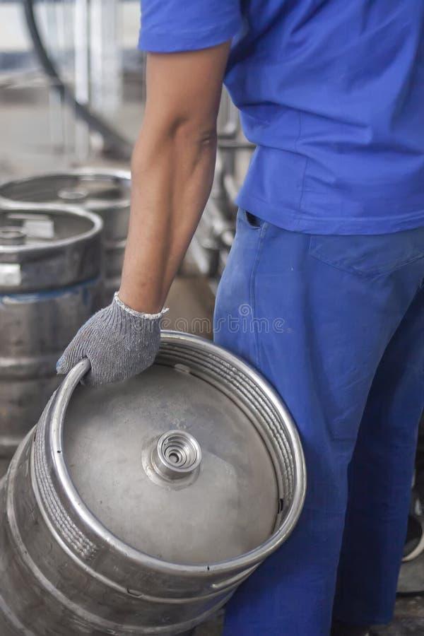 Obsługuje stawiać piwne baryłki na linii produkcyjnej w fabryce zdjęcia stock