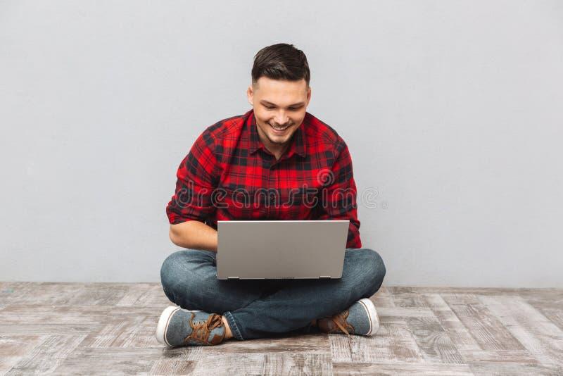 Obsługuje studenckiego działanie na laptopie podczas gdy siedzący na podłoga zdjęcie royalty free