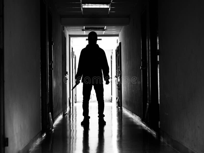 Obsługuje sylwetkę chodzącą z nożem w świetle otwarcia drzwi w ciemnym pokoju daleko od, zagrożenia pojęcie zdjęcie stock