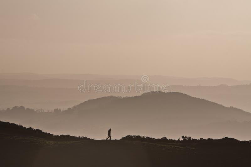 Obsługuje trekking na górze z mgławym różowym tłem zdjęcia stock