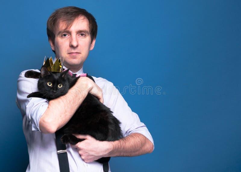 Obsługuje trzymać ślicznego czarnego kota w błyszczącej złotej koronie zdjęcia stock