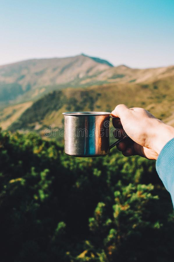 Obsługuje trzymać filiżankę gorąca kawa w górach Halny tło zdjęcia royalty free