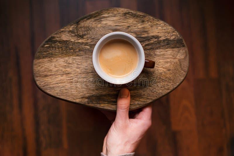 Obsługuje trzymać filiżanka kawy na drewnianym, rocznika tło Ręka trzyma kubek kawa młody biznesmen Roczników brzmienia obraz stock