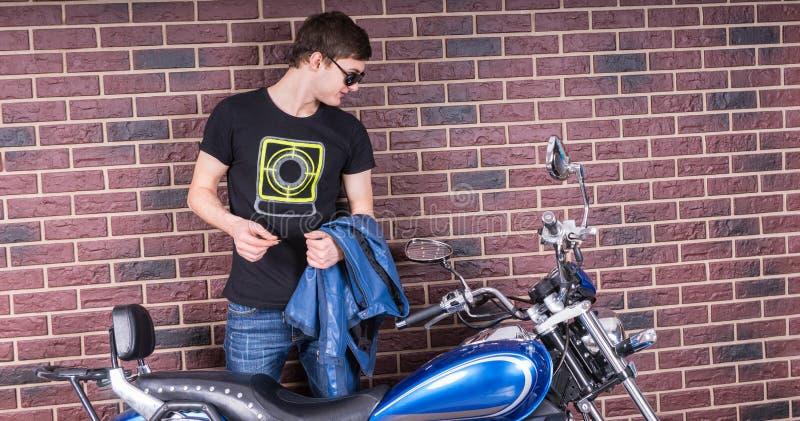 Obsługuje Trzymać kurtkę Patrzeje jego motocykl obraz royalty free