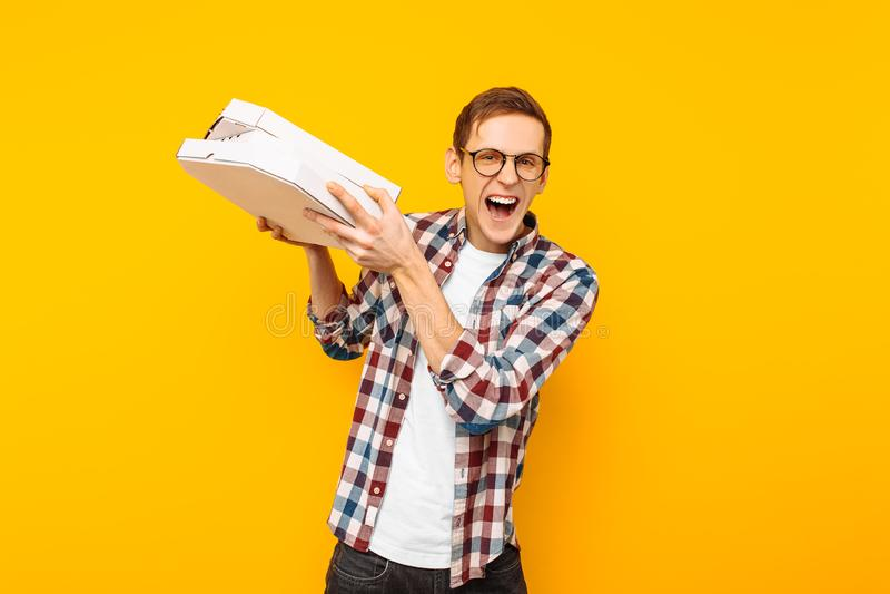 Obsługuje trzymać pudełko pizza na żółtym tle obrazy royalty free