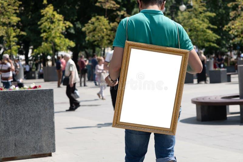 obsługuje trzymać pustą białą deskę na jego z powrotem zdjęcia stock