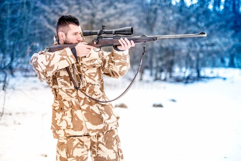 Obsługuje trzymać snajperskiego karabin i celowanie przy wrogiem na polu bitwy fotografia stock