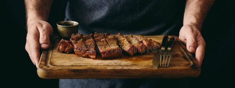 Obsługuje trzymać soczystą piec na grillu wołowina stku tnącą deskę obraz stock