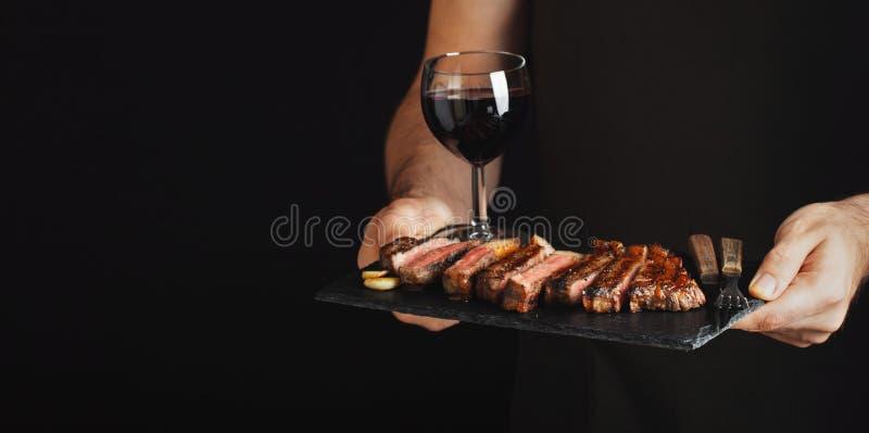 Obsługuje trzymać soczystego piec na grillu wołowina stek z pikantność i czerwonego wina szkłem na kamiennej tnącej desce na czar obraz royalty free