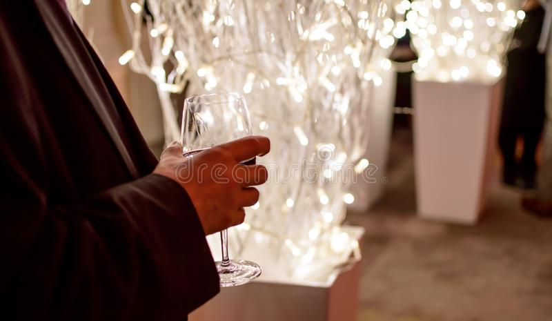 Obsługuje trzymać szkło wino przy wakacyjnymi bożymi narodzeniami lub nowego roku biznesu przyjęciem obrazy stock