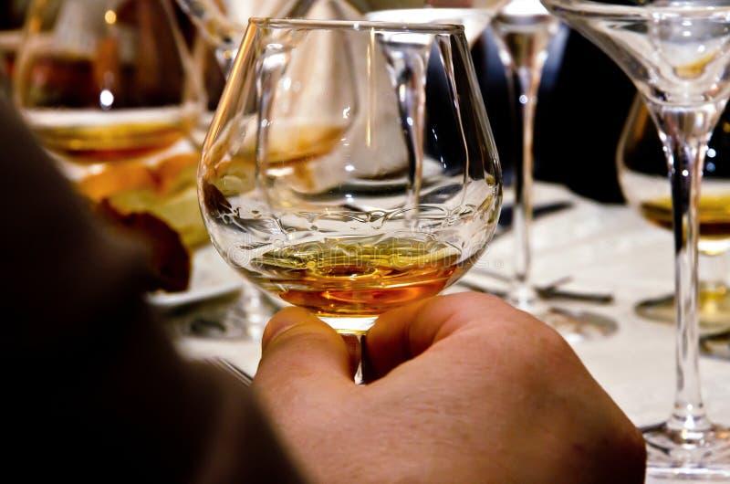 Obs?uguje trzyma? szklany z whisky przy sto?em, zamyka w g?r?, zdjęcia royalty free