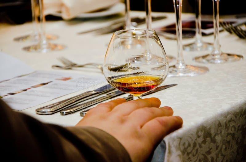 Obs?uguje trzyma? szklany z whisky przy sto?em, zamyka w g?r?, obraz stock