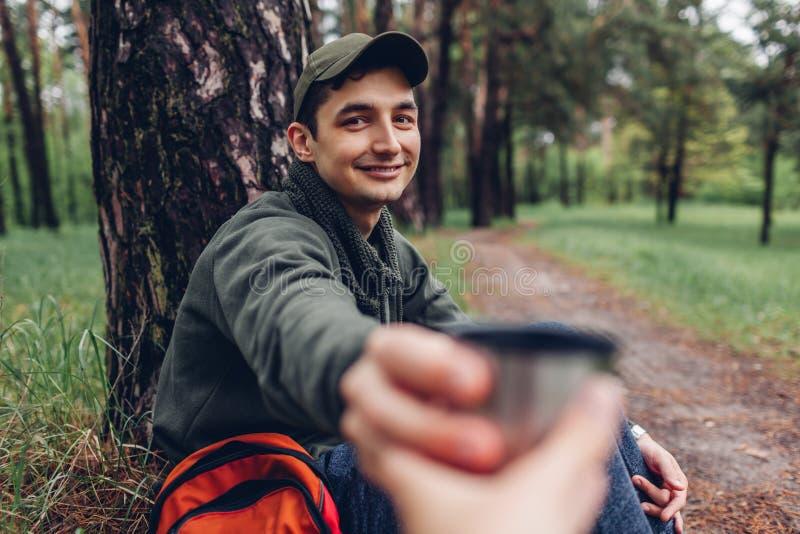 Obsługuje turystyczną daje filiżankę gorąca herbata jego przyjaciel w wiosna lasowym campingu, podróżować i sporta pojęciu, obraz stock