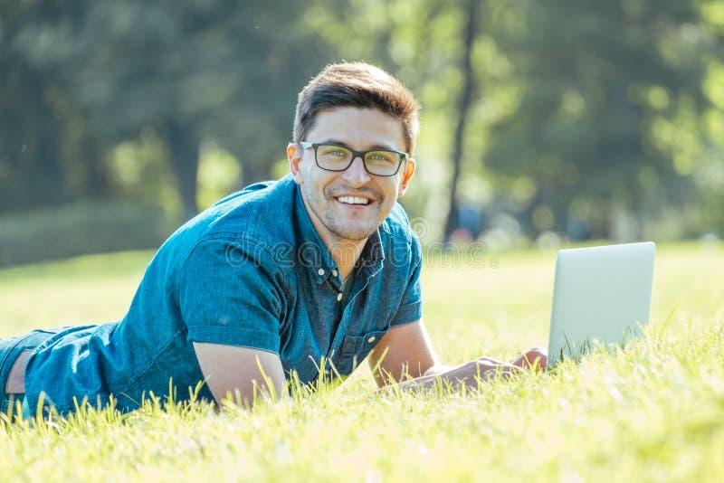 Obsługuje używać laptop w miasto parku fotografia stock