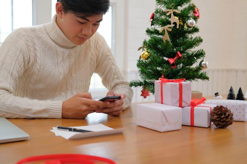 Obsługuje używać mobilnego mądrze telefon z boże narodzenie dekoracją xmas nowy obraz stock