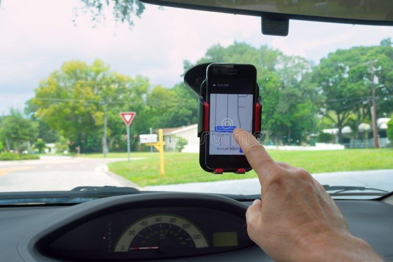 Obsługuje używać smartphone telefon komórkowego w właściciel kołysankowej górze na przedniej szybie w samochodzie zdjęcia stock