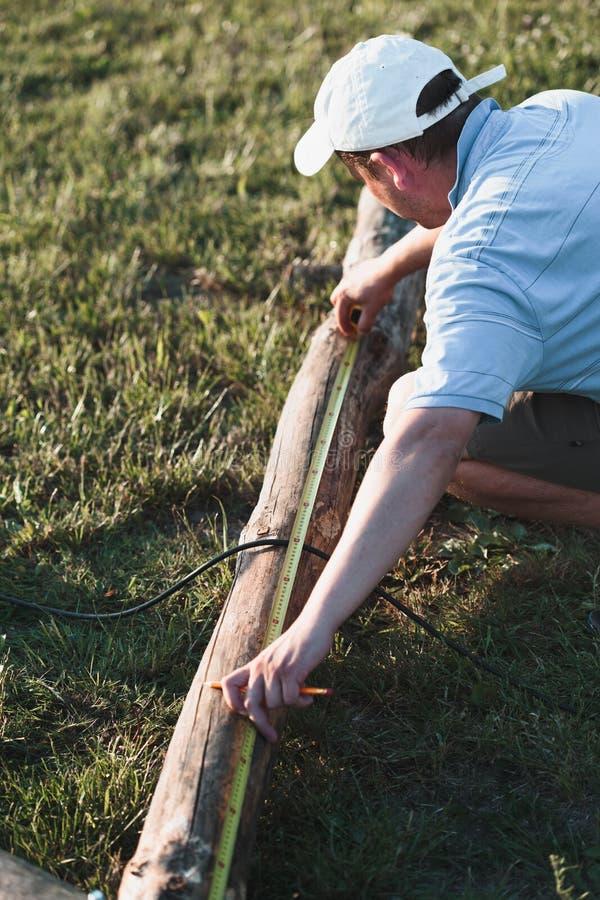 Obsługuje używać stalową taśmy miarę mierzyć szalunek w ogródzie podczas gdy pracujący zdjęcia stock
