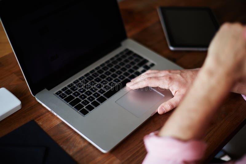 Obsługuje use laptopu obsiadanie przy drewnianym biurkiem z ręką przeciw jego usta obrazy royalty free