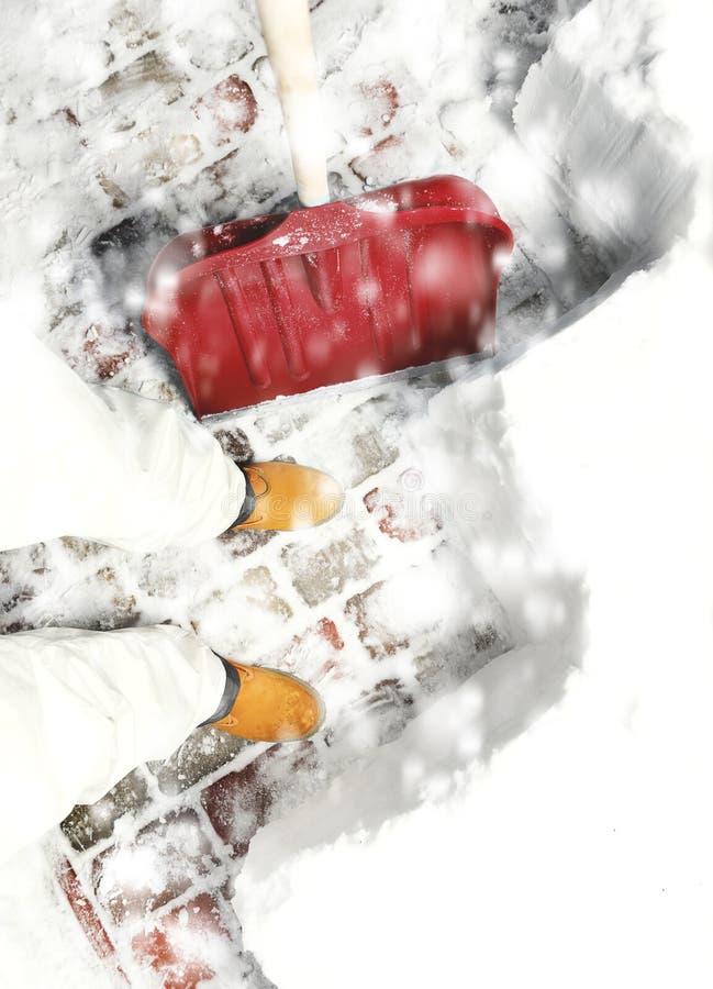 Obsługuje usuwać śnieg na podwórku z łopatą podczas opadu śniegu zdjęcia royalty free