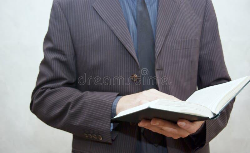 Obsługuje w kostiumu trzyma otwartą książkę obrazy stock