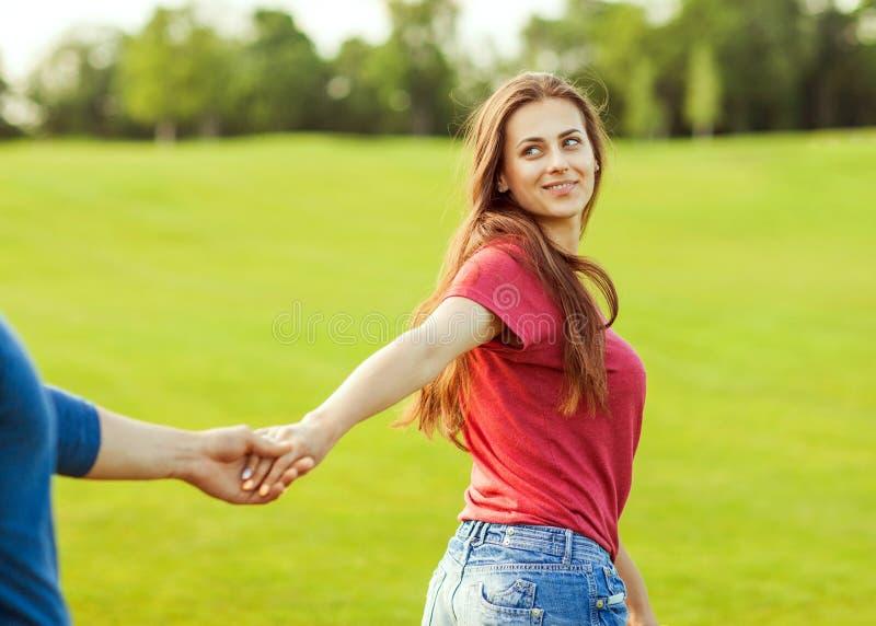 Obsługuje w miłości trzyma rękę dziewczyna i chodzą w parku zdjęcie stock
