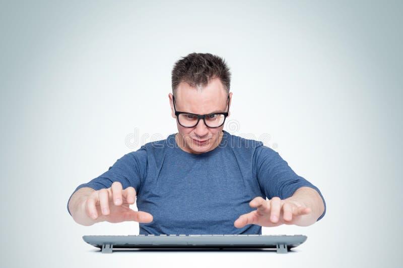 Obsługuje w szkła działaniu przy komputerem, jego ręki unosi się nad klawiaturą podczas gdy pisać na maszynie, na lekkim tle Fron obraz stock