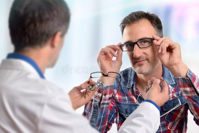 Obsługuje wybierać parę szkła w eyewear sklepie obraz stock