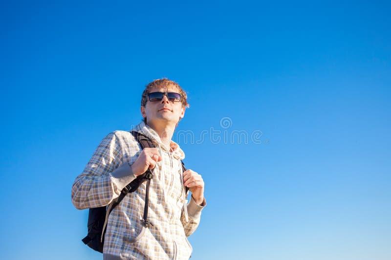 Obsługuje wycieczkowicza mienia plecaka na słonecznym dniu przeciw niebieskiemu niebu zdjęcie royalty free