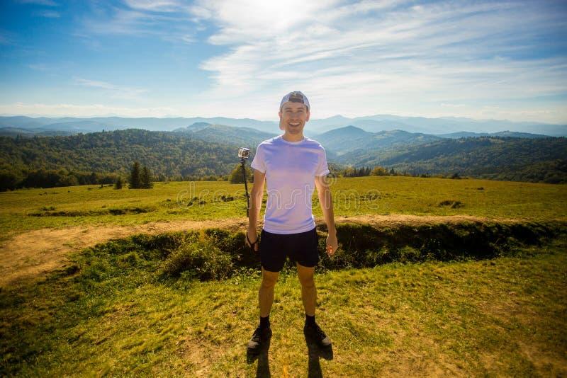 Obsługuje wycieczkowicza relaksuje na górze wzgórza i podziwia pięknego halnego dolinnego widok obraz royalty free