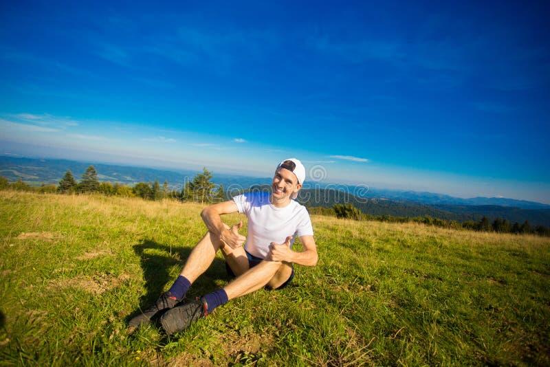 Obsługuje wycieczkowicza relaksuje na górze wzgórza i podziwia pięknego halnego dolinnego widok obrazy stock
