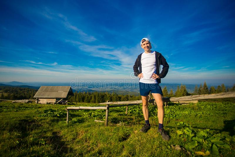 Obsługuje wycieczkowicza relaksuje na górze wzgórza i podziwia pięknego halnego dolinnego widok zdjęcia stock