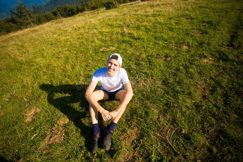 Obsługuje wycieczkowicza relaksuje na górze wzgórza i podziwia pięknego halnego dolinnego widok obraz stock