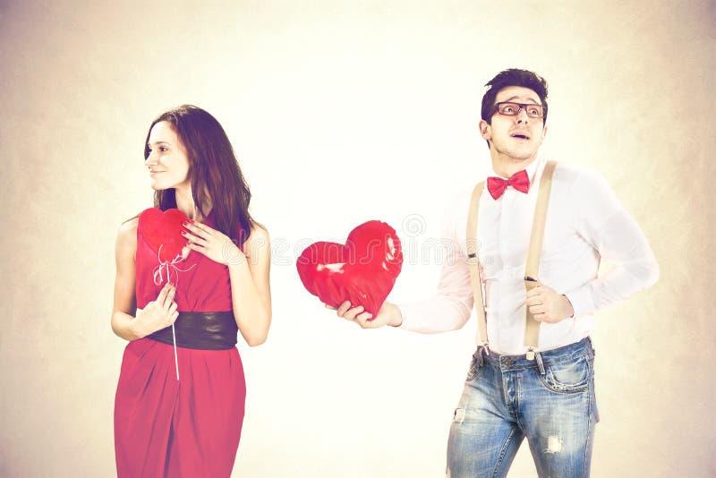 Obsługuje zbliżać się kobiety daje ona czerwonym kierowym kształtów balonom w valentine ` s dniu zdjęcie royalty free