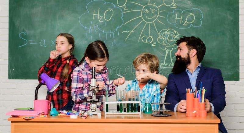 Obs?uguje brodatego nauczyciela i uczni z pr?bnymi tubkami w sali lekcyjnej Szkolny chemii lab Nauka wymaga teori? szko?a fotografia royalty free