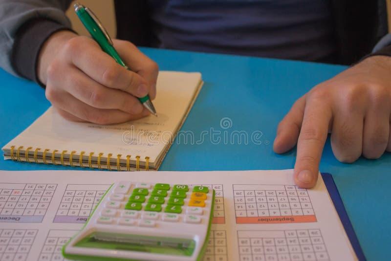 Obs?uguje dzia?anie przy biurowym biurkiem, on u?ywa kalkulatora M??czyzna robi jego ksi?gowo?ci zdjęcia royalty free