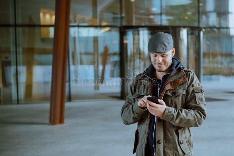 Obs?uguje komunikowa? z jego telefonem kom?rkowym w jego miastowym ?yciu Komunikacji, technologii i styl ?ycia poj?cie, zdjęcie royalty free
