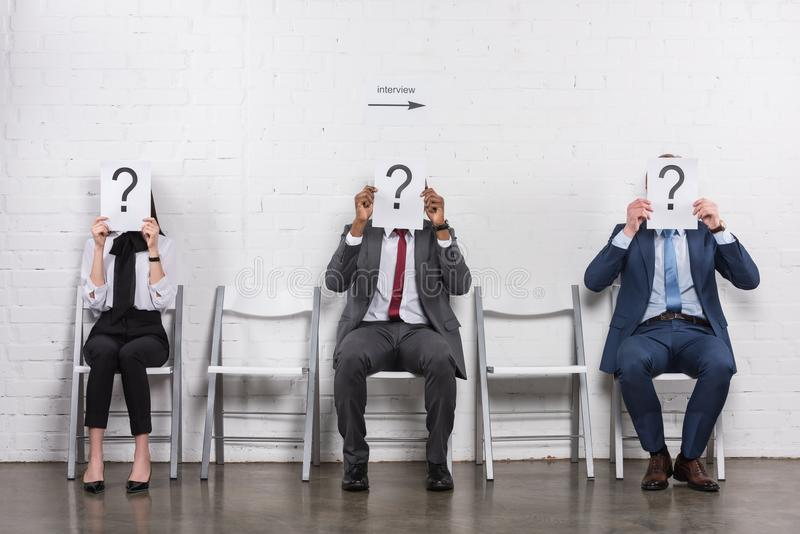 obscured view of multicultural business people holding cards with question marks while waiting stock photo