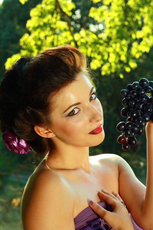 Obscuridade da mulher - uvas azuis foto de stock