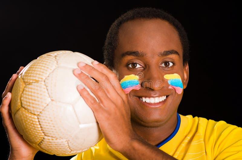 A obscuridade do Headshot descascou o homem que veste a camisa amarela do futebol na frente do fundo preto, pintura facial da ban imagens de stock royalty free