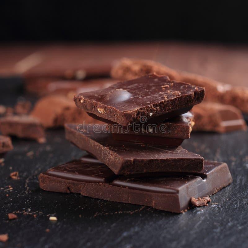 Obscuridade e barras e partes de chocolate do leite na placa de pedra preta imagens de stock royalty free