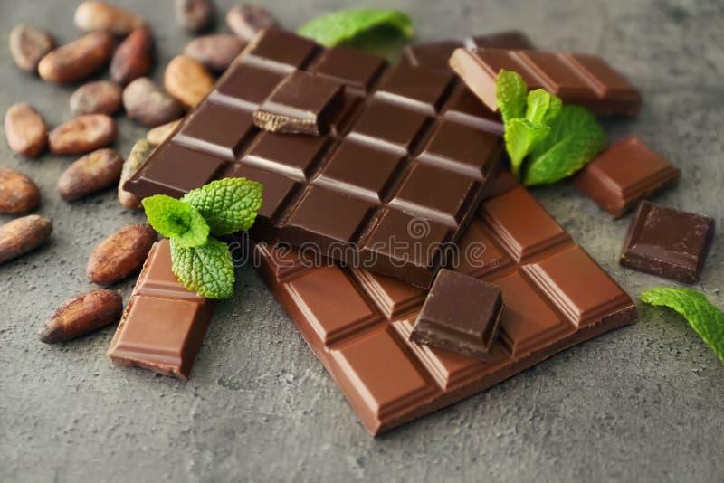 Obscuridade e chocolate de leite no fundo cinzento fotografia de stock