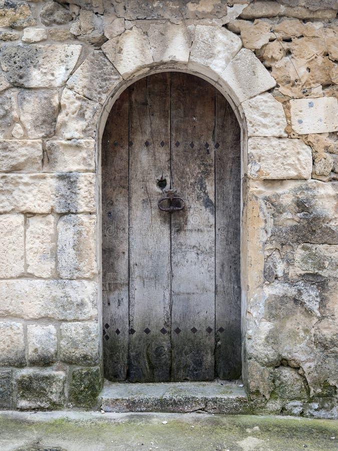 A obscuridade muito velha arqueou a porta de madeira na parede antiga da pedra calcária da casa em france fotos de stock