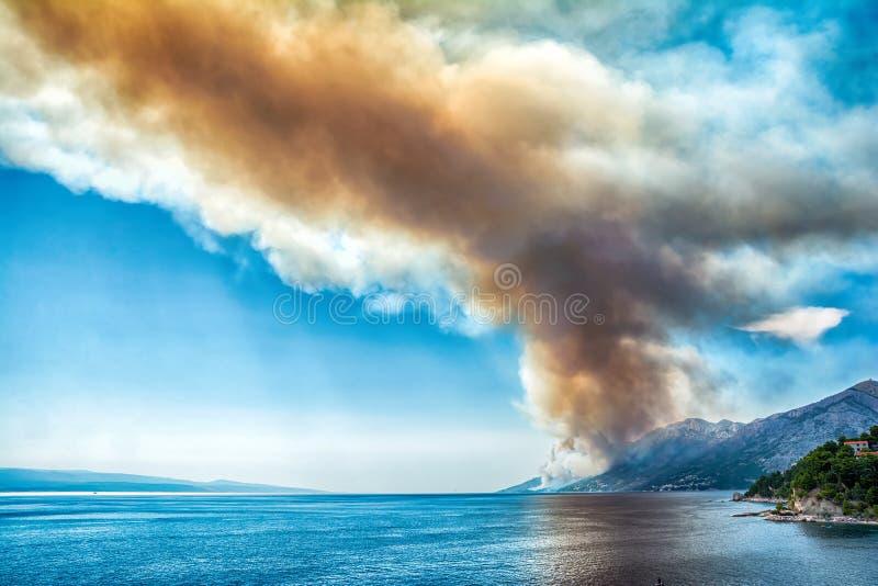 Obscuridade perigosa - fumo e poeira vermelhos sobre o mar Floresta ardente da montanha no fogo Costa adriático em Croatia DISA d fotografia de stock
