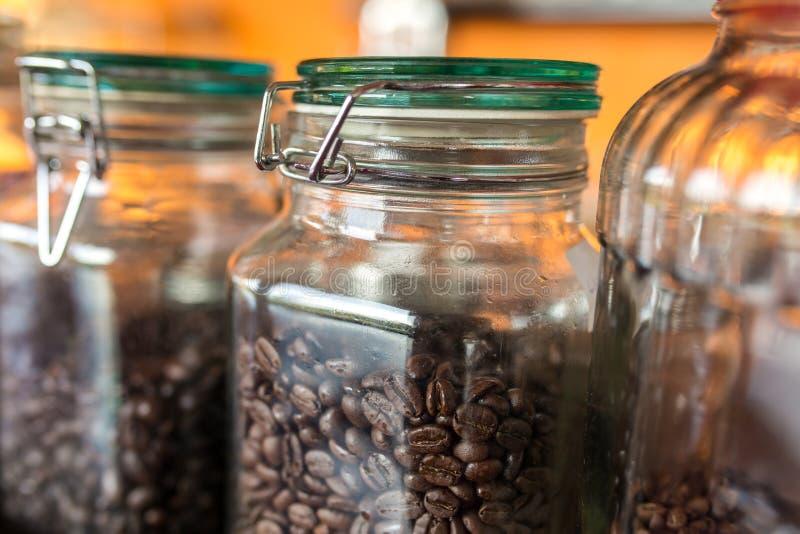 A obscuridade roasted feijões de café em um frasco do vidro fotos de stock royalty free